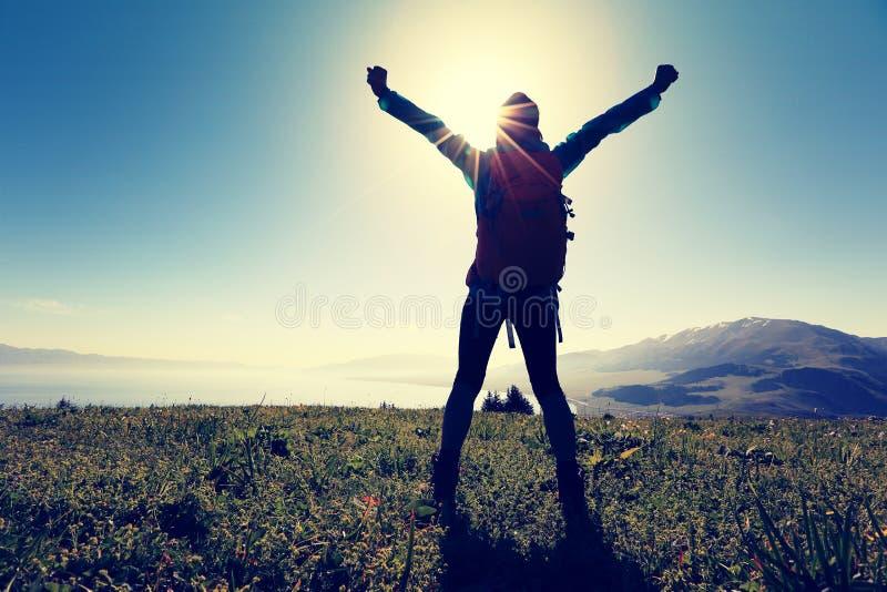 Braços abertos do mochileiro bem sucedido da mulher no pico de montanha imagem de stock royalty free