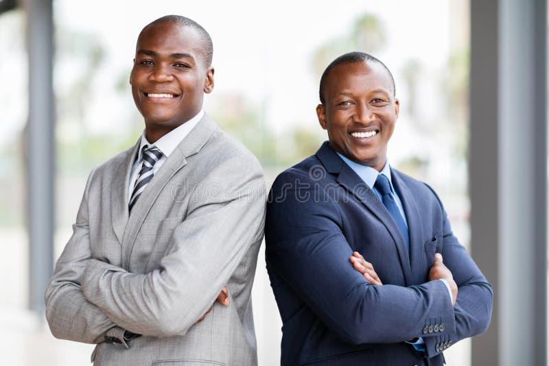 braços africanos dos homens de negócios cruzados foto de stock