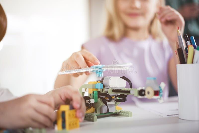 Braços das crianças que criam o helicóptero do construtor fotografia de stock royalty free
