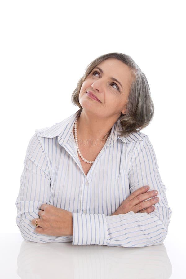 Braços de dobramento da mulher de cabelo cinzenta superior e memórias afeiçoadas, dreami foto de stock royalty free