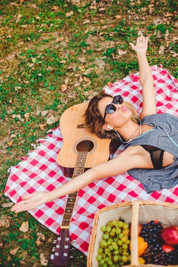 Braços de escuta da música da menina, amuar e espalhar em um piquenique imagem de stock royalty free
