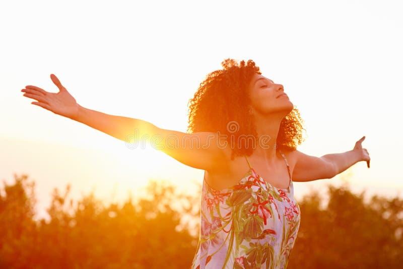 Braços estendido da mulher em uma expressão da liberdade com sunflar imagem de stock