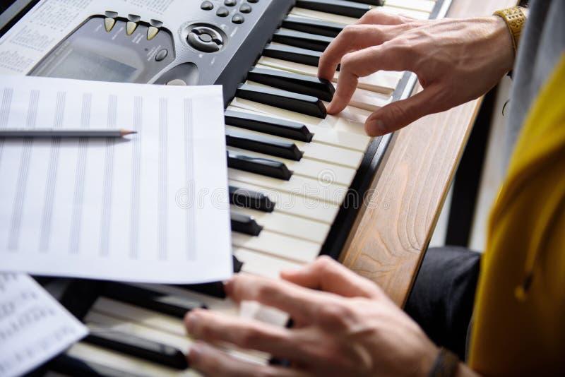 Braços masculinos que tocam em chaves do piano bonde imagens de stock royalty free