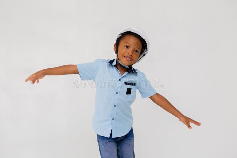 Braços outstretching vestindo do capacete do capacete de segurança do menino pré-escolar afro-americano fotos de stock