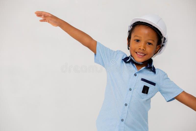 Braços outstretching vestindo do capacete do capacete de segurança do menino pré-escolar afro-americano imagem de stock royalty free