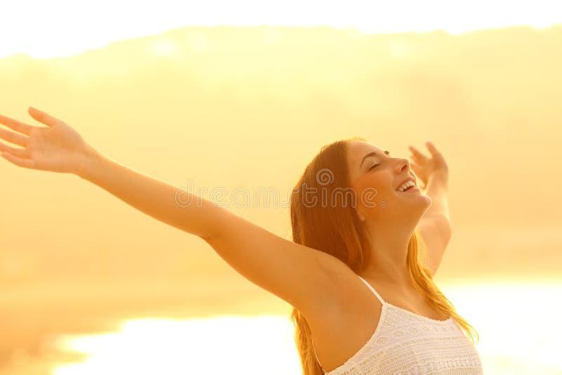 Braços trstching da mulher feliz que respiram o ar fresco no por do sol fotos de stock