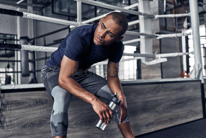Brać czas odpoczywać Przystojnego młodego Afrykańskiego mężczyzna w sporta clothin zdjęcia stock