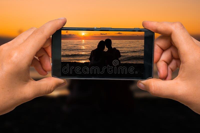 Brać fotografię kochająca para przy zmierzchem z telefonem komórkowym zdjęcia royalty free