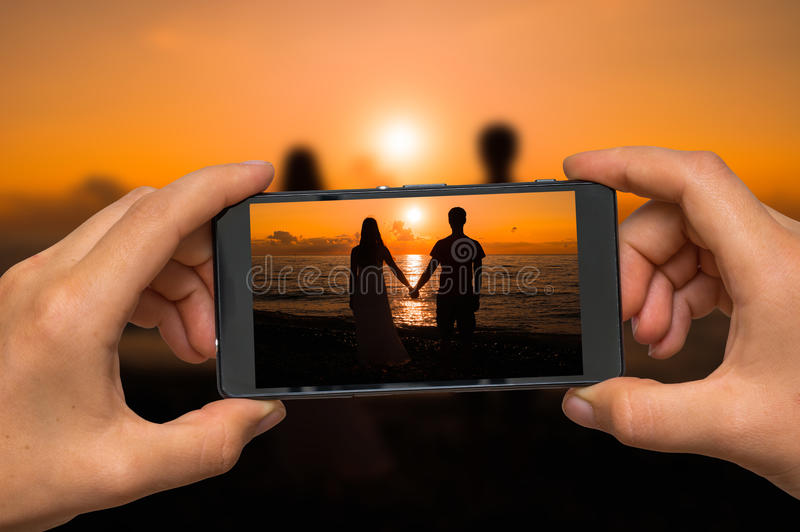 Brać fotografię kochająca para przy zmierzchem z telefonem komórkowym zdjęcie stock