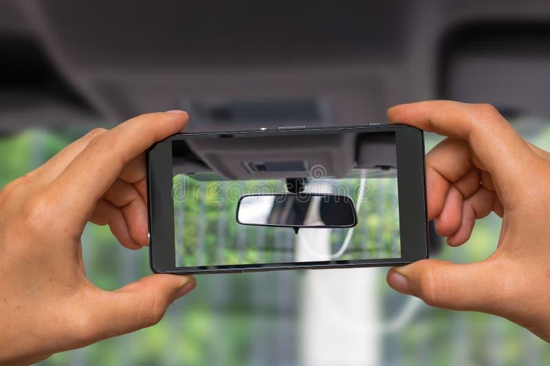 Brać fotografię samochodowy rearview lustro z telefonem komórkowym obrazy stock