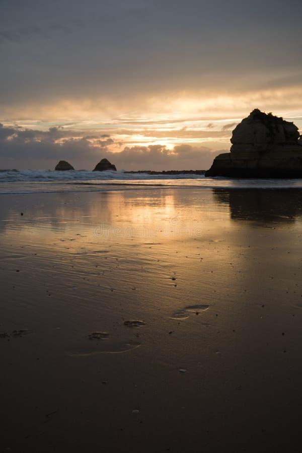 Brać fotografie piękny zmierzch na piaskowatej plaży z falezami odbija w wodzie fotografia stock