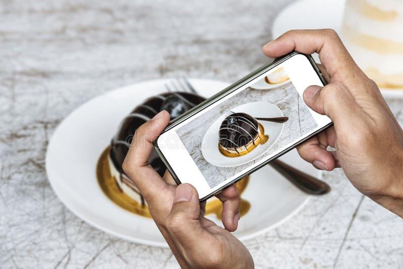 Brać karmową fotografię mądrze telefonem, deserowa fotografia, ciemny słodki czekoladowy tort zdjęcie stock