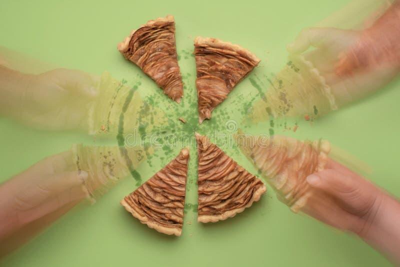 Brać kulebiaków plasterki Ręki podnosi jabłczanego kulebiaka kawałki t?o plama zamazywa? chwyta frisbee doskakiwania ruch zdjęcie stock