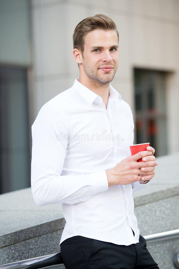 Brać moment cieszy się dzień Mężczyzna dobrze przygotowywająca biała koszula pije kawowego miastowego tło Biznesmen relaksuje z k obraz royalty free