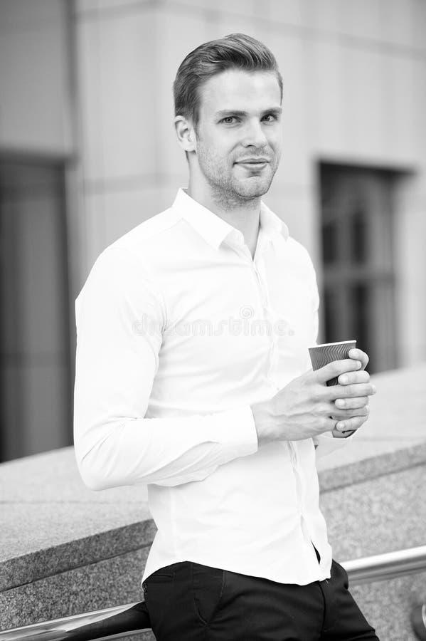 Brać moment cieszy się dzień Mężczyzna dobrze przygotowywająca biała koszula pije kawowego miastowego tło Biznesmen relaksuje z k zdjęcie royalty free