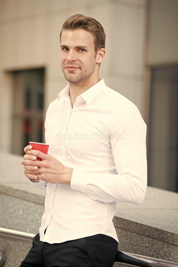Brać moment cieszy się dzień Mężczyzna dobrze przygotowywająca biała koszula pije kawowego miastowego tło Biznesmen relaksuje z k obrazy royalty free