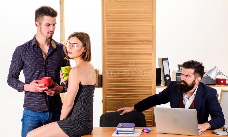 Brać przerwę na lunch Partnery biznesowi cieszy się rozmowę w przerwie na lunch podczas gdy kolega pracuje w tle Dwa obraz stock