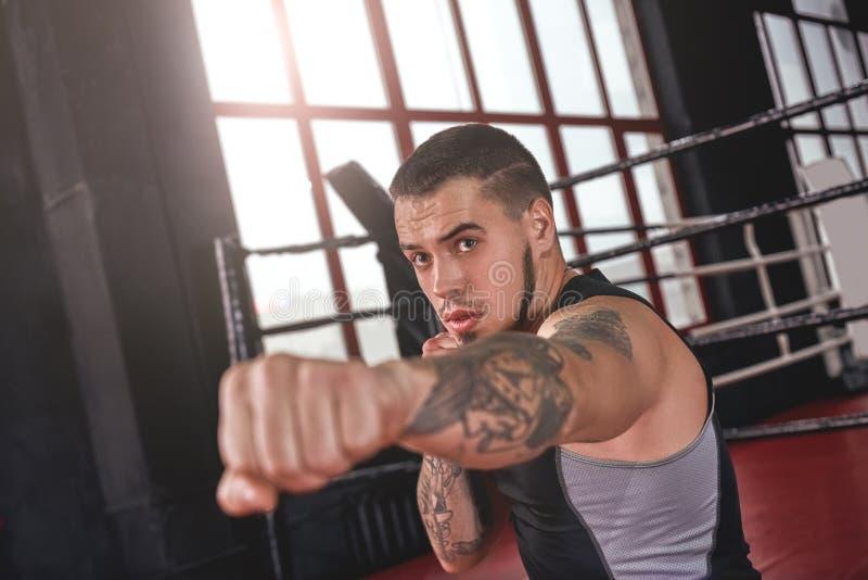 Bra jab Muskulös idrottsman nen i sportar som beklär kasta jabstansmaskin i boxningidrottshall Säker boxare som gör skugga-boxnin royaltyfri fotografi