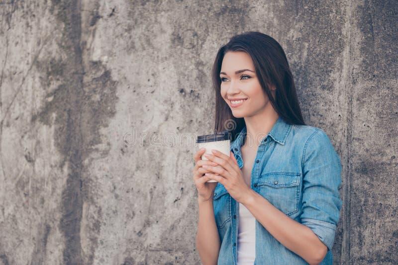 Bra morgon! Den gladlynta nätta unga fridfulla brunettdamen har varmt te nära betongväggen utanför, att le som bär hemtrevlig cas arkivbilder