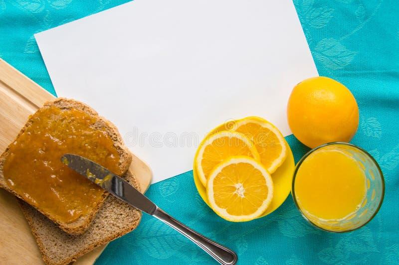 Bra morgon med orange fruktsaft, bröd och driftstopp royaltyfria bilder