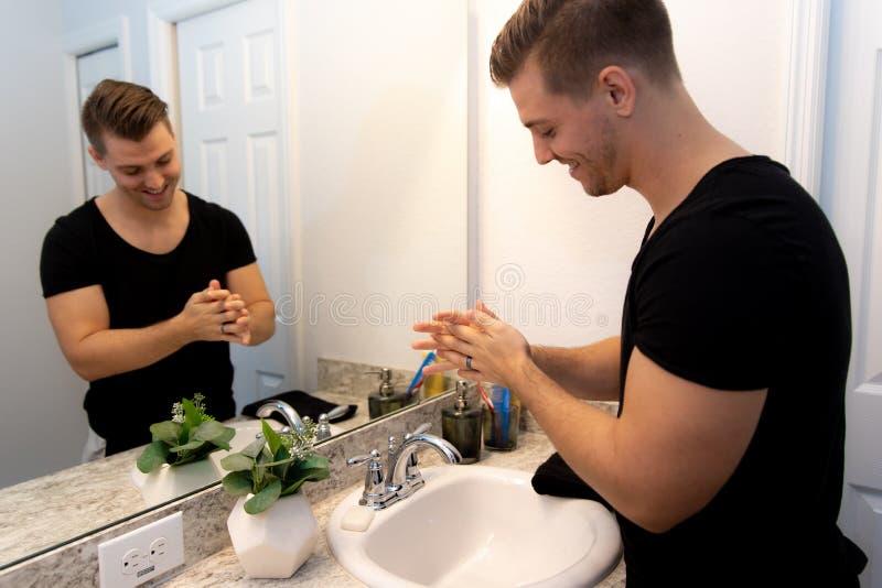 Bra seende händer och framsida i hem- badrumspegel och vask för ung man som tvättande får ren och ansad under morgonrutin arkivfoton