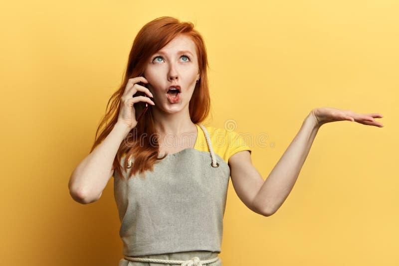 Bra seende hemmafru som skvallrar, medan tala med hennes bästa vän arkivbilder