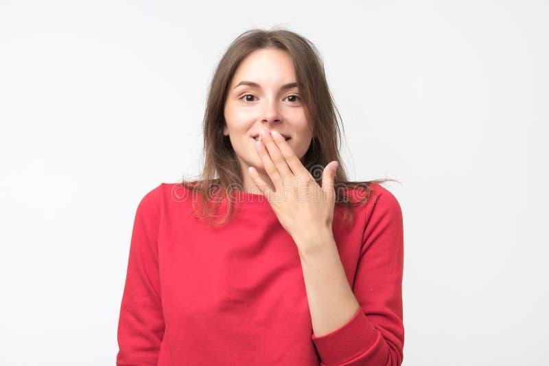 Bra seende unga kvinnliga fniss joyfully, täcker munnen, som försök stoppar att skratta arkivbild