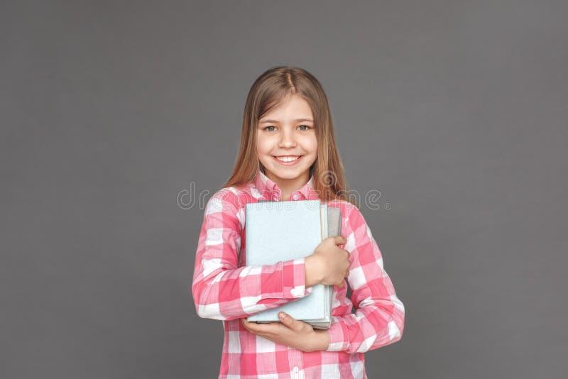 Bra skolflicka Flickaanseende som isoleras på grå färger med högen av att le för böcker som tätt är glat royaltyfri foto