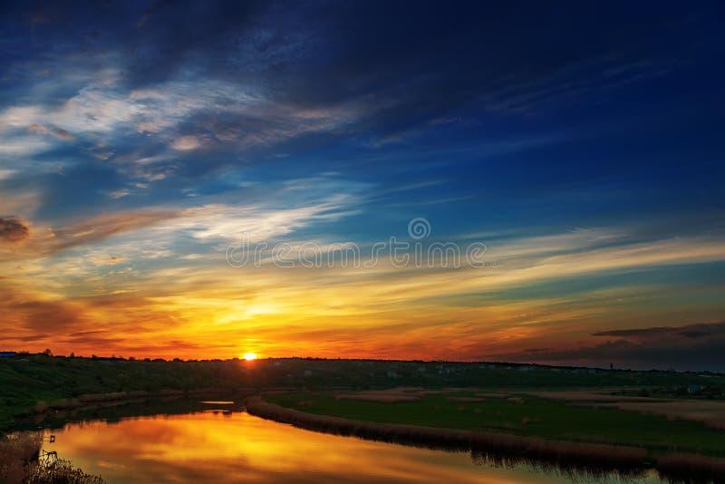 Bra solnedgång i moln över floden arkivfoton
