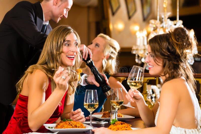 Uppassaren kryddar matställen i en fin restaurang royaltyfria foton