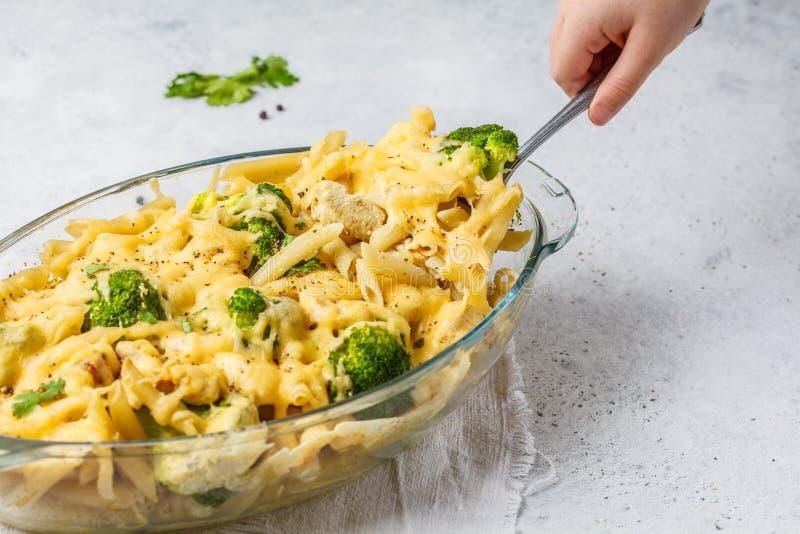 Braadpan met deegwaren, kippen, broccoli en kaaskorst in een gl stock fotografie