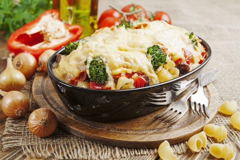 Braadpan met vlees, deegwaren, broccoli en tomaten stock afbeelding
