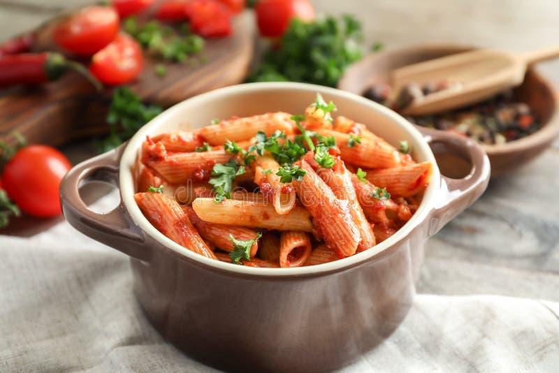 Braadpan van smakelijke pennedeegwaren met tomatensaus op lijst royalty-vrije stock foto's
