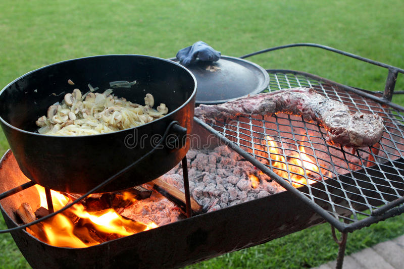 Braai with meat and a cast iron pot. Braai or barbecue with meat and a cast iron pot over a fire royalty free stock photo