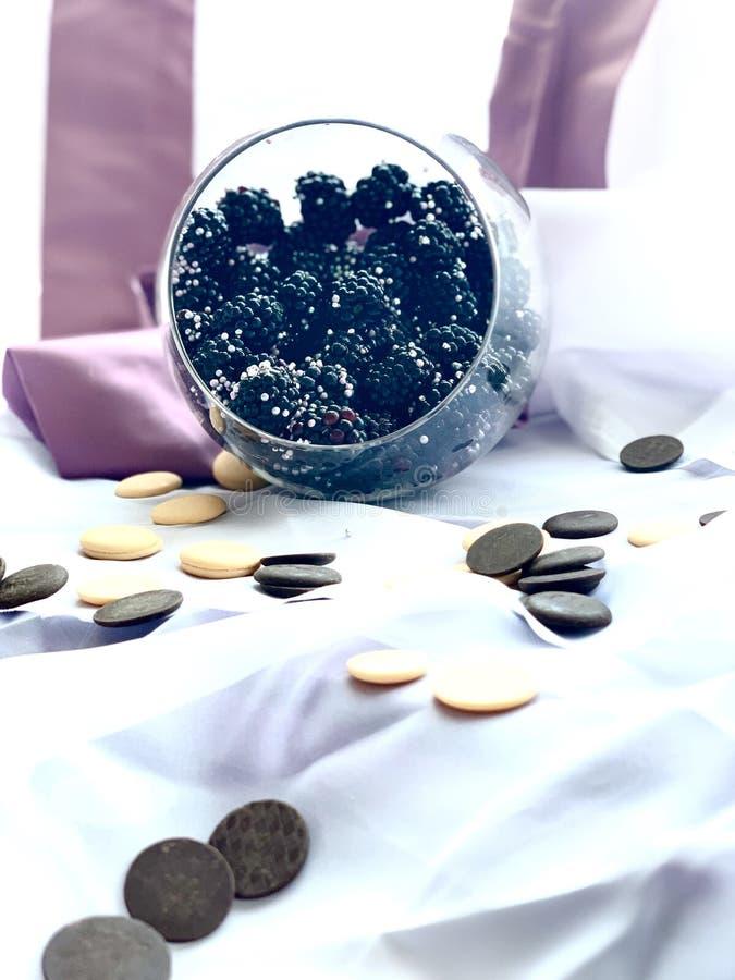 Braambessen in een glas, met zilveren dragee Witte, zwarte chocolade van ronde vorm Wit-lilac achtergrond royalty-vrije stock afbeelding