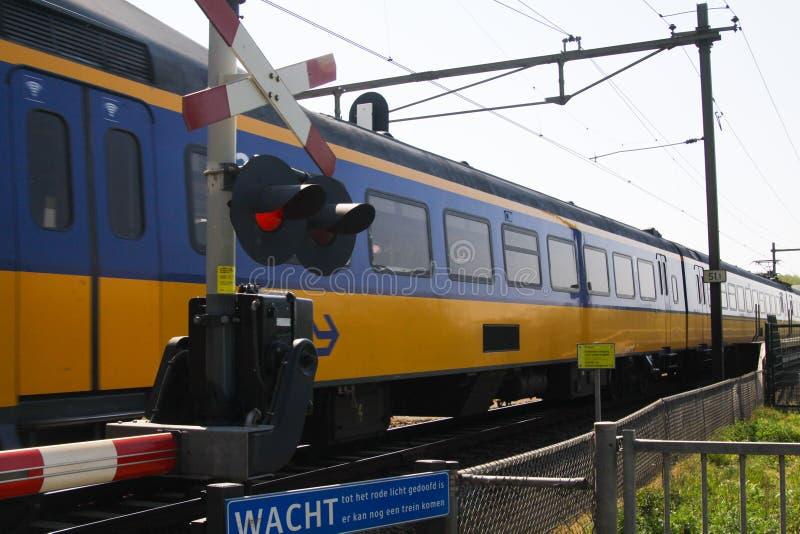 BRABANT NÄRA NIJMEGEN, NEDERLÄNDERNA - APRIL 21 2019: Sikt på det kommande holländska drevet på järnvägkorsningen med barriären royaltyfria foton