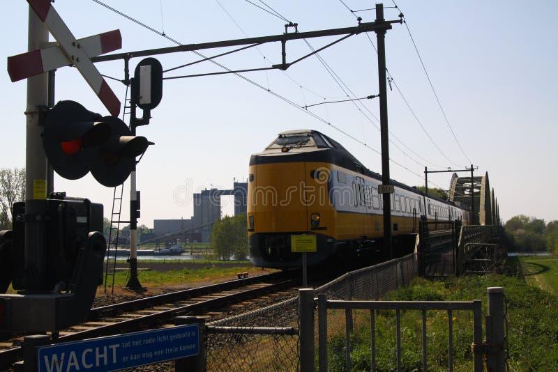 BRABANT PRÈS DE NIMÈGUE, PAYS-BAS - 21 AVRIL 2019 : Vue sur le prochain train néerlandais au croisement de chemin de fer avec la  images stock