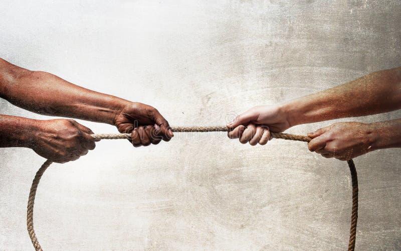 Braccia neri di etnia con la corda di trazione delle mani contro la persona caucasica bianca della corsa nel razzismo di arresto  fotografia stock libera da diritti