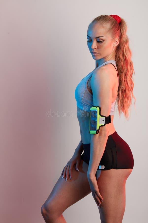 Bracciale d'uso della giovane donna sexy con lo Smart Phone immagini stock libere da diritti