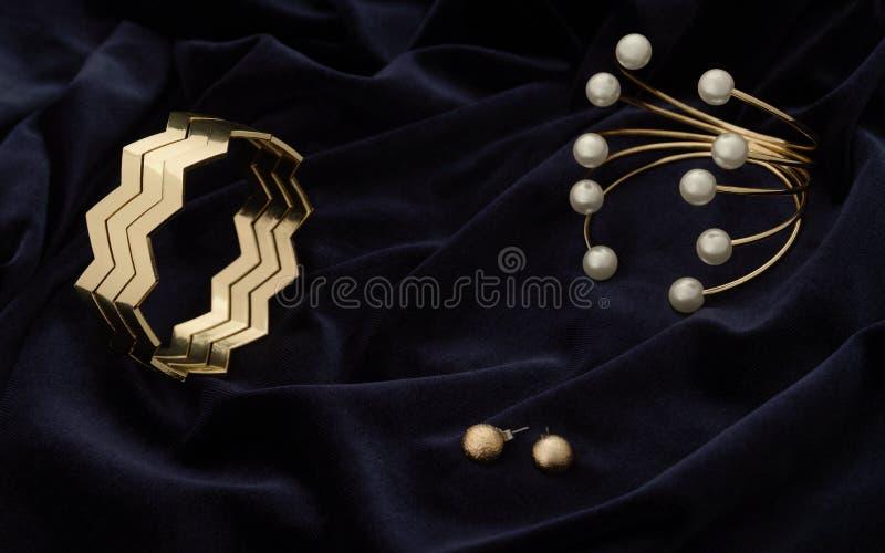 Braccialetti moderni dorati e paia degli orecchini sul tessuto blu scuro del velluto fotografie stock libere da diritti