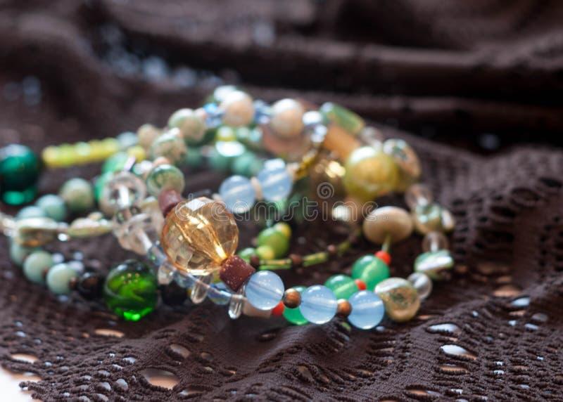 Braccialetti multicolori con le perle su pizzo marrone fotografie stock libere da diritti