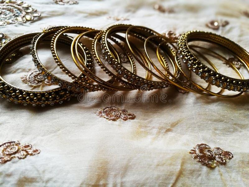 Braccialetti progettati differenti dell'oro nel fondo di seta fotografia stock