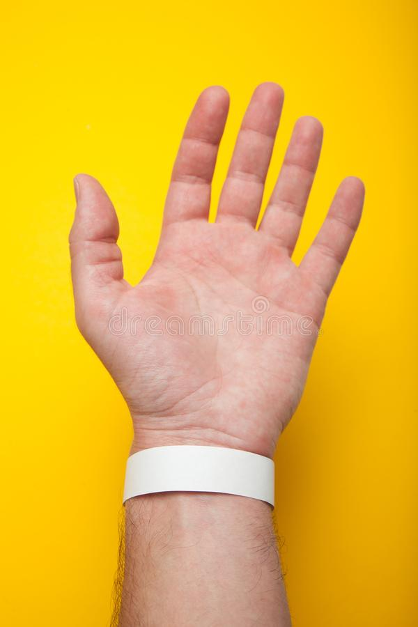 Braccialetto in bianco del modello a disposizione, isolato su fondo giallo Polsino della carta di concerto fotografie stock libere da diritti