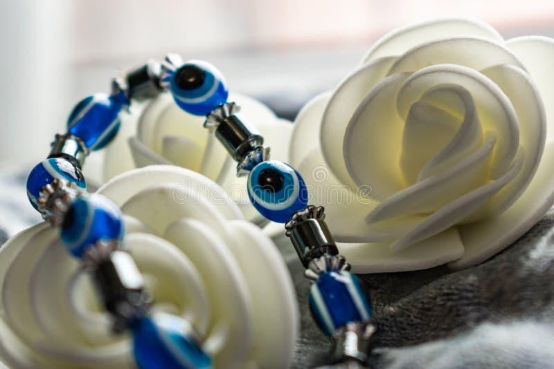Braccialetto blu fatto delle pietre naturali per il giorno delle donne, l'8 marzo Figura sotto forma di occhi e di pupilla dal ma fotografia stock