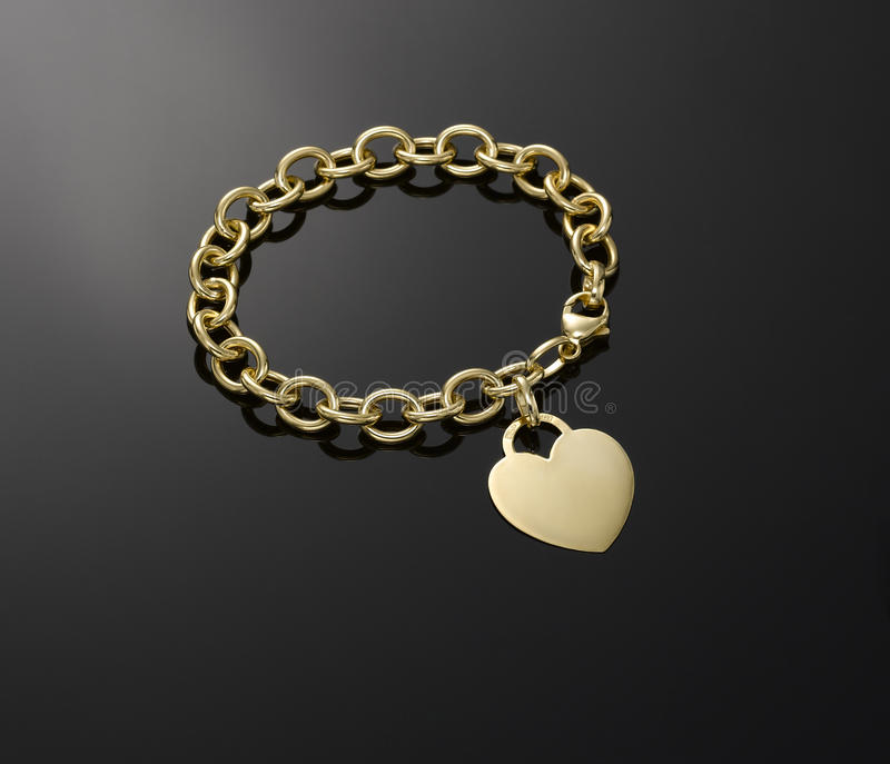 Braccialetto del pendente del cuore dell'oro immagine stock libera da diritti