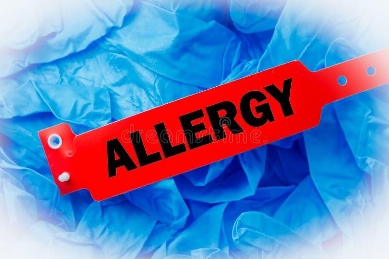 Braccialetto di allergia sopra il guanto protettivo blu fotografia stock