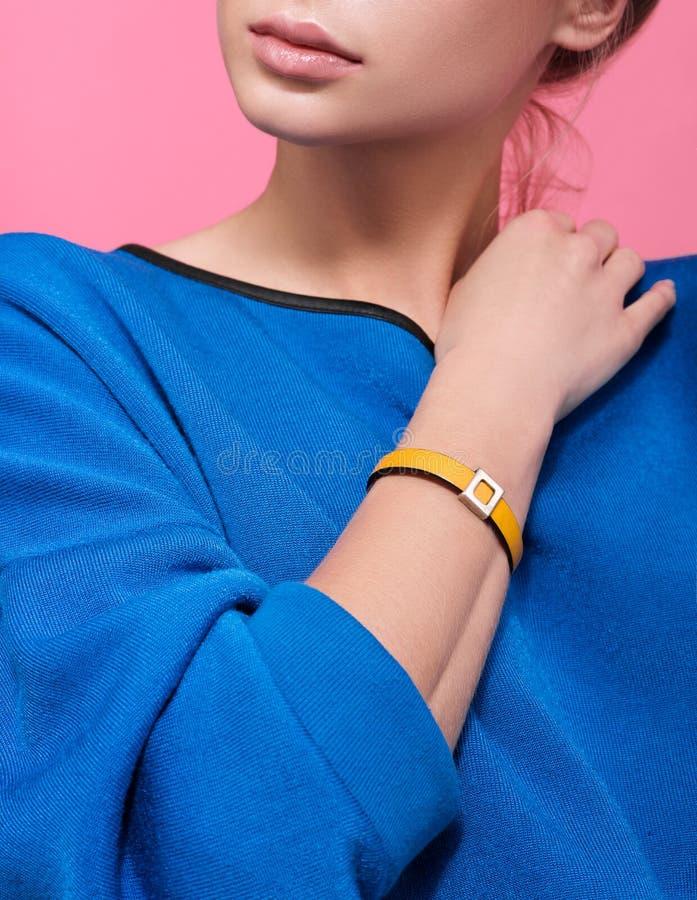 Braccialetto di cuoio giallo sul braccio di una giovane donna Accessori fatti a mano immagine stock libera da diritti