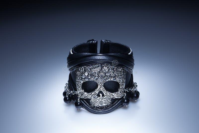 Braccialetto di cuoio nero con il pendente del cranio del metallo e pietre nere fotografia stock