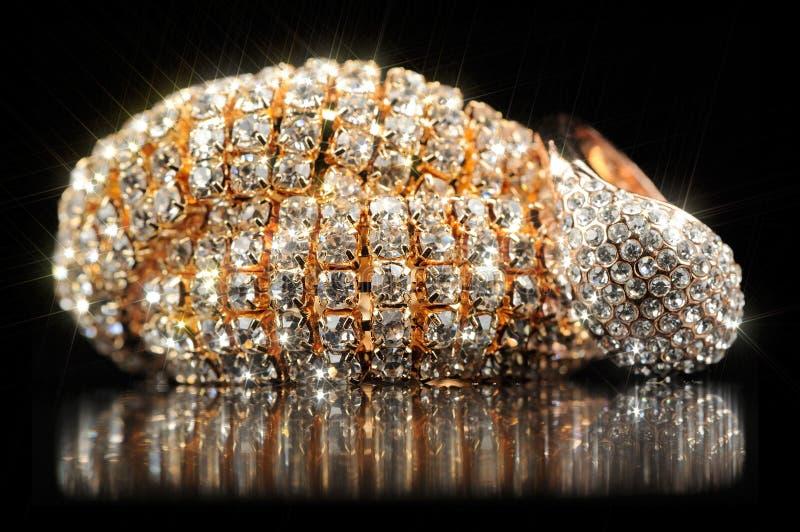 Braccialetto ed anello brillanti dell'oro su fondo nero immagini stock