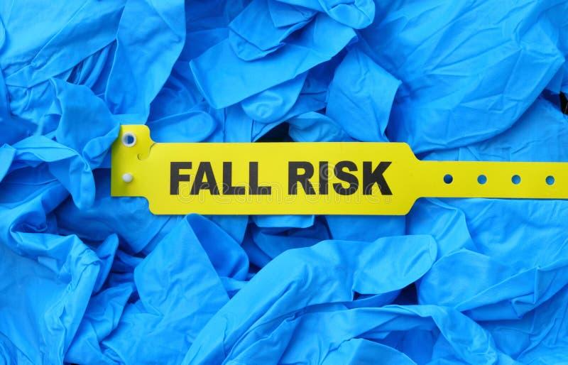 Braccialetto giallo di rischio di caduta sui guanti dell'ospedale fotografia stock